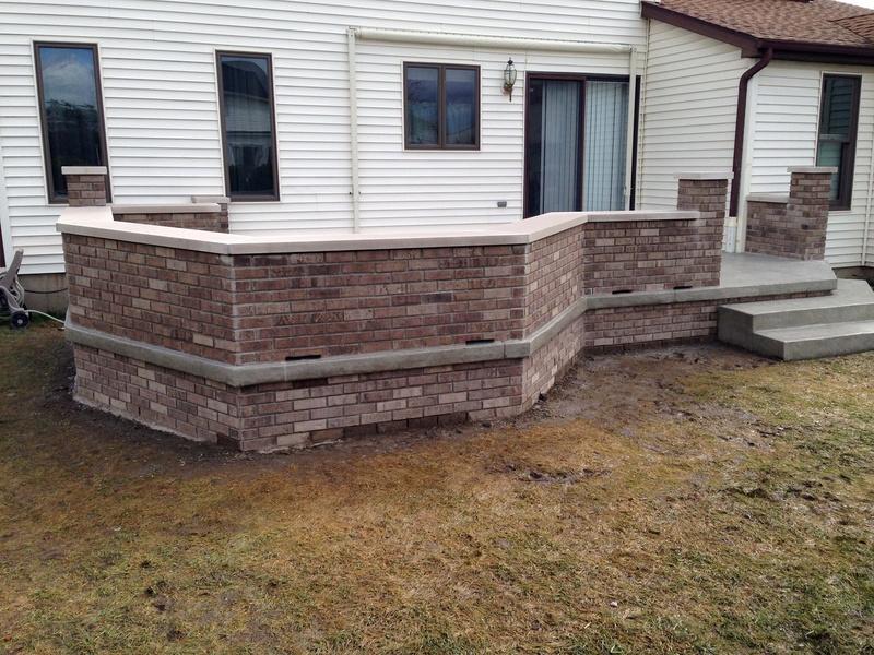Raised Stamped Concrete Patio With Decorative Brick Walls.